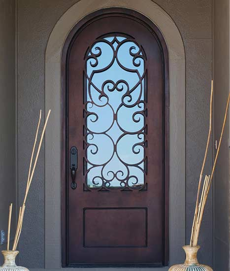 Custom single round top iron door entry, Tudor style, Patented Thermal Break, red copper finish, clear glass
