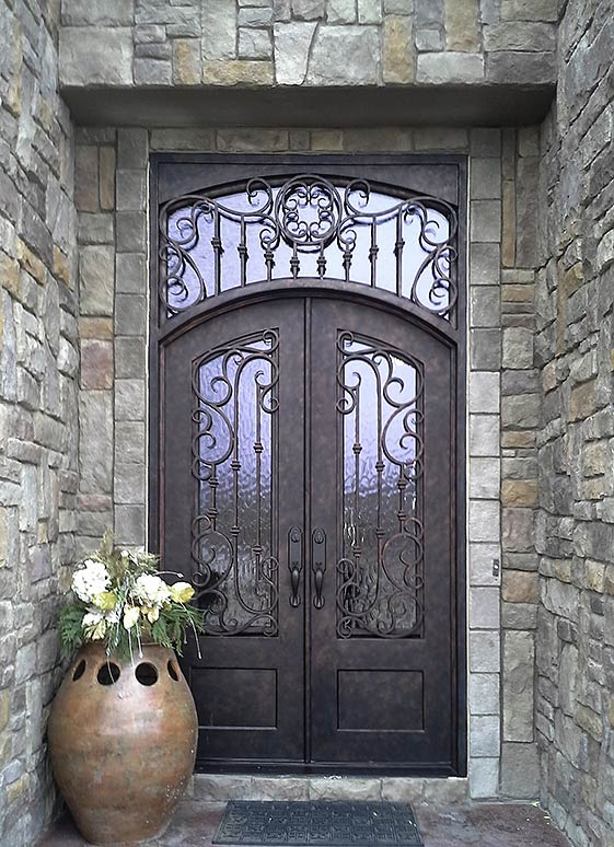 "Custom Iron double door entry, Tuscan style, arched top, transom, Flemish glass, ¾"" glass panels, operable iron grill, hand rubbed bronze finish, Patented Thermal Break"